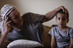 Ali Kinno comforts his son Ahmad at a temporary apartment in the coastal town of Jiyeh, south of Beirut, Lebanon, Tuesday, Sept. 15, 2020. The Kinno family from Syria's Aleppo region was devastated in the wake of the Aug. 4 explosion at the Beirut port -- Hoda, 11, suffered a broken neck and other injuries and her sister Sedra, 15, died in the explosion. (AP Photo/Hassan Ammar)