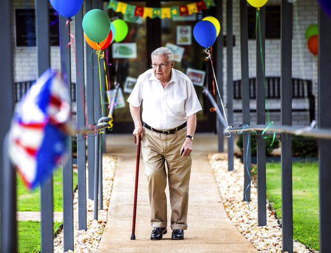 Roger McNeece walks past decorations while leaving to beat the incoming rain as Muscle Shoals Senior Living Center opens to guests on Tuesday, June 8, 2021 in Muscle Shoals, Ala. (Dan Busey/The TimesDaily via AP)