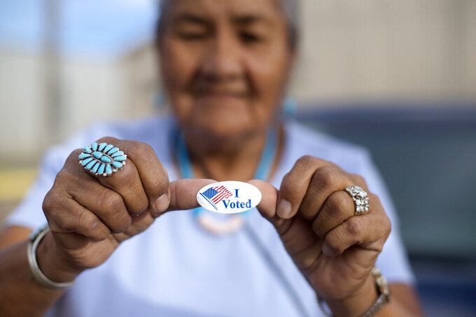 """FILE - In this Aug. 28, 2018, file photo, Mildred James of Sanders, Arizona, shows off her """"I Voted"""" sticker as she awaits election results in Window Rock, Arizona, on the Navajo Nation. The tribe says bills recently signed into Arizona law would make voting more difficult than it already is on the vast reservation. (AP Photo/Cayla Nimmo, File)"""