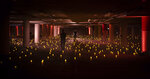 """This image released by the Lyric Opera of Chicago shows 2,880 battery-powered candles arrayed in an underground parking garage in this scene from Lyric Opera's """"Twilight: Gods,"""" an adaptation of Wagner's """"Göttertdämmerung"""" in Chicago. (Kyle Flubacker/Lyric Opera of Chicago via AP)"""