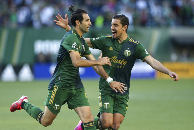 Portland Timbers midfielder Diego Valeri, left, and defender Josecarlos Van Rankin celebrate after Valeri scores his 100th MLS goal, against Los Angeles FC during the first half of an MLS soccer match Wednesday, July 21, 2021, in Portland, Ore. (Sean Meagher/The Oregonian via AP)