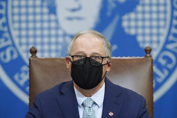 Washington Gov. Jay Inslee wears a mask as he speaks at a news conference, Tuesday, Jan. 5, 2021, at the Capitol in Olympia, Wash. Inslee said some COVID-19 restrictions in Washington will be eased beginning next week and the state will change its reopening plan to move from a county-based oversight system to one focused on regions. (AP Photo/Ted S. Warren)