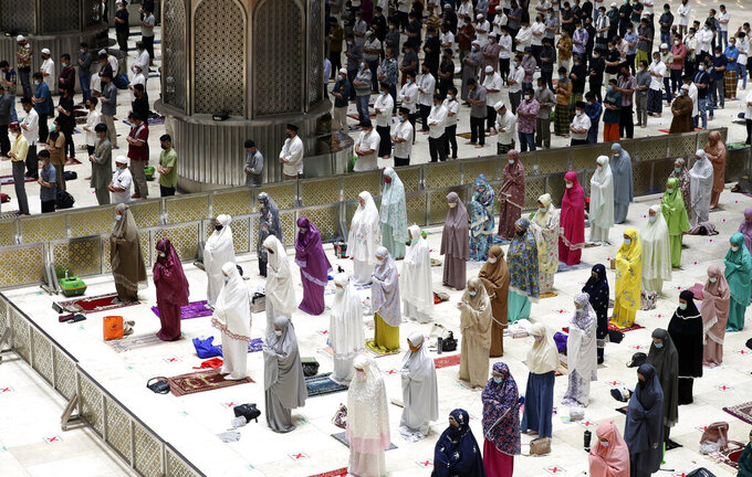 """Indonesian Muslims pray spaced apart as they practice social distancing to curb the spread of the new coronavirus during an evening prayer called """"tarawih"""" marking the first eve of the holy fasting month of Ramadan at Istiqlal Mosque in Jakarta, Indonesia. Monday, April 12, 2021. During Ramadan, the holiest month in Islamic calendar, Muslims refrain from eating, drinking, smoking and sex from dawn to dusk. (AP Photo/ Achmad Ibrahim)"""