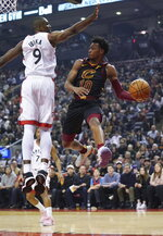 Cleveland Cavaliers' Darius Garland (10) passes around the defense of Toronto Raptors' Serge Ibaka during the first half of an NBA basketball game Tuesday, Dec. 31, 2019, in Toronto. (Hans Deryk/The Canadian Press via AP)