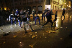 Anti-government protesters throw stones at the riot police during ongoing protests against the political elites who have ruled the country for decades, in Beirut, Lebanon, in Beirut, Lebanon, Wednesday, Jan. 22, 2020. (AP Photo/Hassan Ammar)