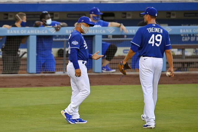 Los Angeles Dodgers manager Dave Roberts, left, talks with relief pitcher Blake Treinen during an intrasquad baseball game Wednesday, July 8, 2020, in Los Angeles. (AP Photo/Mark J. Terrill)