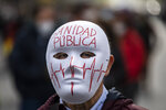 A demonstrator attends a protest to demand more resources for public health system in Madrid, Spain, Sunday, Nov. 29, 2020. The organizers delivered a manifesto to the Madrid regional authorities demanding the end privatization of the health system. The mask reads in Spanish