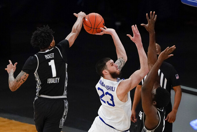 Georgetown's Jamorko Pickett (1) blocks a shot by Seton Hall's Sandro Mamukelashvili (23) during the first half of an NCAA college basketball game in the semifinals in the Big East men's tournament Friday, March 12, 2021, in New York. (AP Photo/Frank Franklin II)