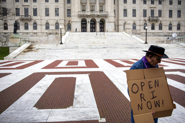 James Dunn stands outside the Statehouse with a handmade sign in favor of reopening the state economy as Gov. Gina Raimondo delivers her daily briefing inside, Friday, May 1, 2020, in Providence, R.I. Raimondo said she still hopes to lift Rhode Island's stay-at-home order in about a week, even though the daily number of new coronavirus cases in the state only appears to have reached a plateau and is not yet on the decline. (AP Photo/David Goldman)