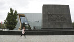 A woman passes the Museum of the History of Polish Jews 'POLIN' in Warsaw, Poland, Tuesday, 16 July 2019. A Jewish association has said that some private donors to Poland's renowned Jewish history museum have suspended their donations out of concern over the government's failure to extend the term of its director. (AP Photo/Czarek Sokolowski)