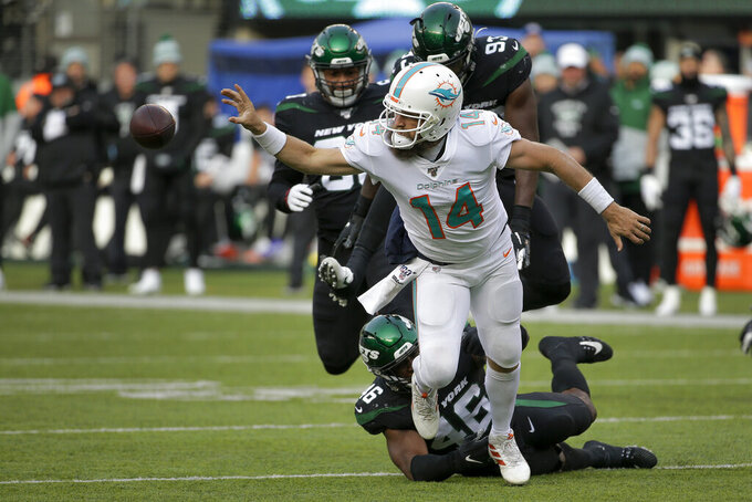 Miami Dolphins quarterback Ryan Fitzpatrick (14) flips a horizontal pass as he is tackled by New York Jets linebacker Neville Hewitt (46) during the second quarter of an NFL football game, Sunday, Dec. 8, 2019, in East Rutherford, N.J. (AP Photo/Seth Wenig)