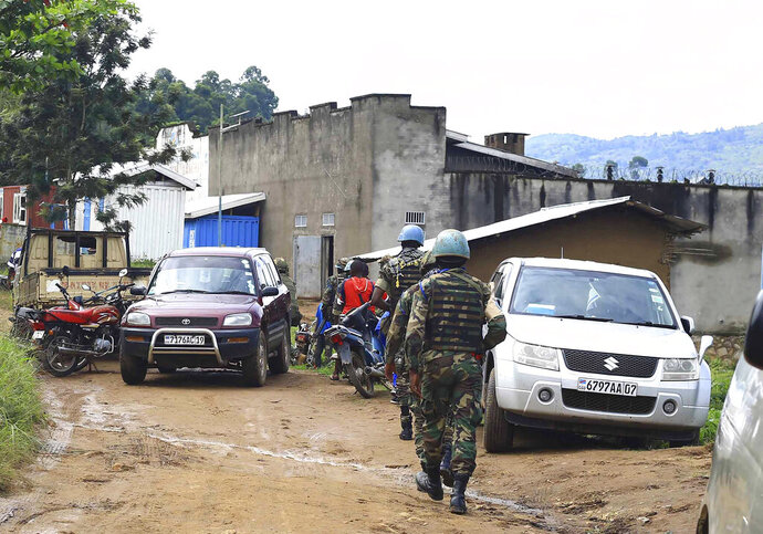 U.N peacekeepers soldiers patrol at the entrance of Kangbay prison in Beni, Congo, Tuesday, Oct. 20. 2020, An official in eastern Congo says more than 1,300 inmates have escaped from the central prison in Beni after an attack by rebels of the Allied Democratic Forces. (AP Photo/Al-hadji Kudra Maliro)