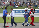 Indianapolis Motor Speedway President Doug Boles, second from left, helps crew members clean up the track after a massive crash caused by a piece of curbing during a NASCAR Series auto race at Indianapolis Motor Speedway, Sunday, Aug. 15, 2021, in Indianapolis. (Bob Ruddick/The Indianapolis Star via AP)
