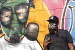 Graffiti artist Angelo Campos poses for a photo by his mural referencing the COVID-19 pandemic which he said he painted in honor of health workers in Rio de Janeiro, Brazil, Thursday, May 21, 2020. Campos, 39, has lost two relatives to the new coronavirus. (AP Photo/Silvia Izquierdo)