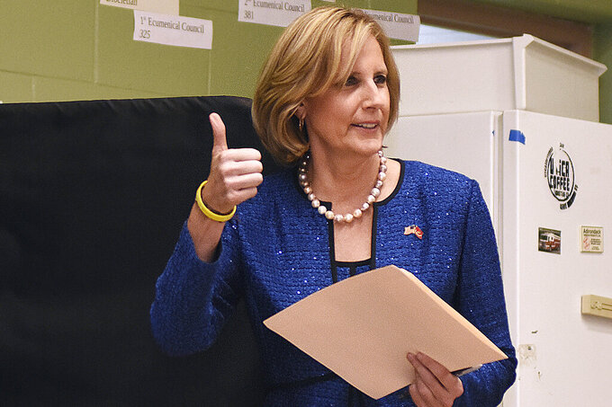 FILE - In this Nov. 6, 2018, file photo, Republican Congresswoman Claudia Tenney signals she successfully cast her ballot after voting at St. George's Church in New Hartford, N.Y.  Tenney appeared on the verge of recapturing her old seat in Congress as election officials wrapped up counting ballots Monday, Feb. 1, 2021, in the nation's last undecided U.S. House race. (AP Photo/Heather Ainsworth, File)