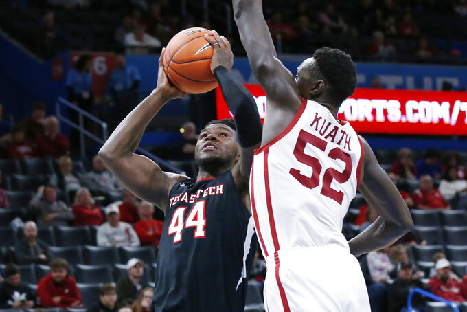Texas Tech guard Chris Clarke (44) goes up for a shot defended by Oklahoma forward Kur Kuath (52) in the second half of an NCAA college basketball game Tuesday, Feb. 25, 2020, in Oklahoma City. (AP Photo/Sue Ogrocki)