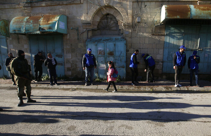 In this Tuesday, Feb. 12, 2019 photo, Palestinian observers, center, watch as children walk past Israeli soldiers on their way to school in the West Bank city of Hebron. Following Israel's expulsion of an international observer force from this volatile West Bank city, Palestinian activists are trying to fill the void by launching their own patrols to document alleged Israeli settler violence. (AP Photo/Majdi Mohammed)