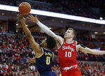 Michigan guard David DeJulius, left, goes up to shoot in front of Ohio State forward Justin Ahrens during the first half of an NCAA college basketball game in Columbus, Ohio, Sunday, March 1, 2020. (AP Photo/Paul Vernon)