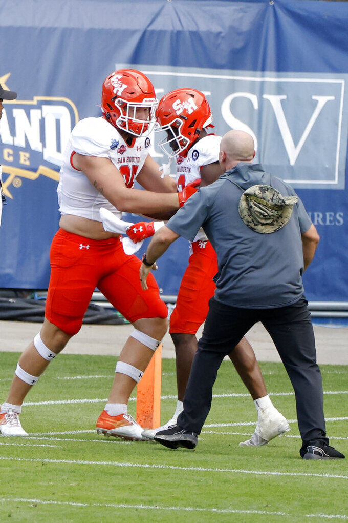 Sam Houston State tight end Rowdy Godwin (85), left, celebrates with wide receiver Ife Adeyi, center, after Adeyi's winning touchdown reception during the second half of the NCAA college FCS Football Championship against South Dakota State in Frisco, Texas, Sunday May 16, 2021. (AP Photo/Michael Ainsworth)