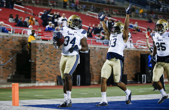 Navy running back Chance Warren (13) celebrates a touchdown by fullback Jamale Carothers (34) during the second half of an NCAA college football game against SMU, Saturday, Oct. 31, 2020, in Dallas. (AP Photo/Brandon Wade)
