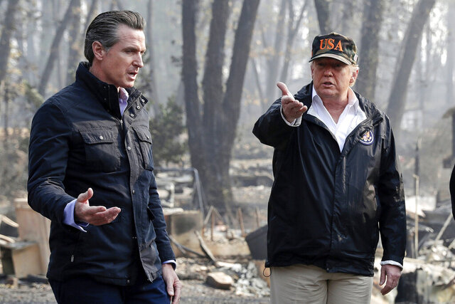 FILE - In this Nov. 17, 2018, file photo, President Donald Trump talks with then California Gov.-elect Gavin Newsom, left, during a visit to a neighborhood impacted by the wildfires in Paradise, Calif. Nearly two years ago President Trump ordered the U.S. Forest Service and the Department of Interior to make federal lands less susceptible to catastrophic wildfires. But the agencies fell short of his goals in 2019, treating a combined 4.3 million acres — just over half of the 8.45 million acres the president sought. It was only slightly better than their average annual performance over nearly two decades, according to government data. (AP Photo/Evan Vucci, File)