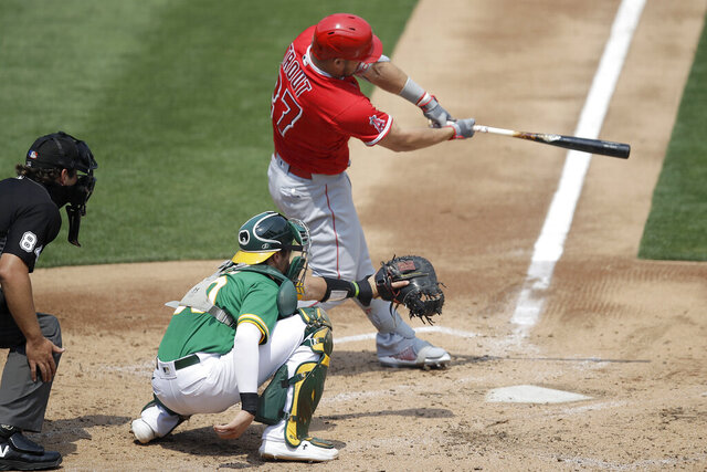 Los Angeles Angels' Mike Trout swings for a two run double off Oakland Athletics' Chris Bassitt in the second inning of a baseball game Saturday, Aug. 22, 2020, in Oakland, Calif. (AP Photo/Ben Margot)