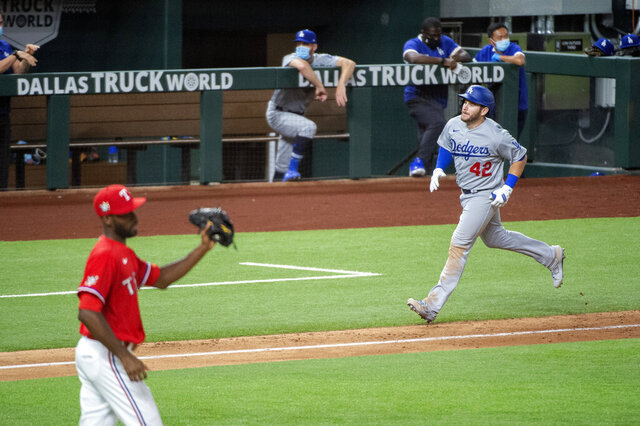 Los Angeles Dodgers' Max Muncy, right, runs toward home on his three-run home run off Texas Rangers relief pitcher Taylor Hearn, left, that also scored Mookie Betts and Corey Seager during the seventh inning of a baseball game Saturday, Aug. 29, 2020, in Arlington, Texas. (AP Photo/Jeffrey McWhorter)