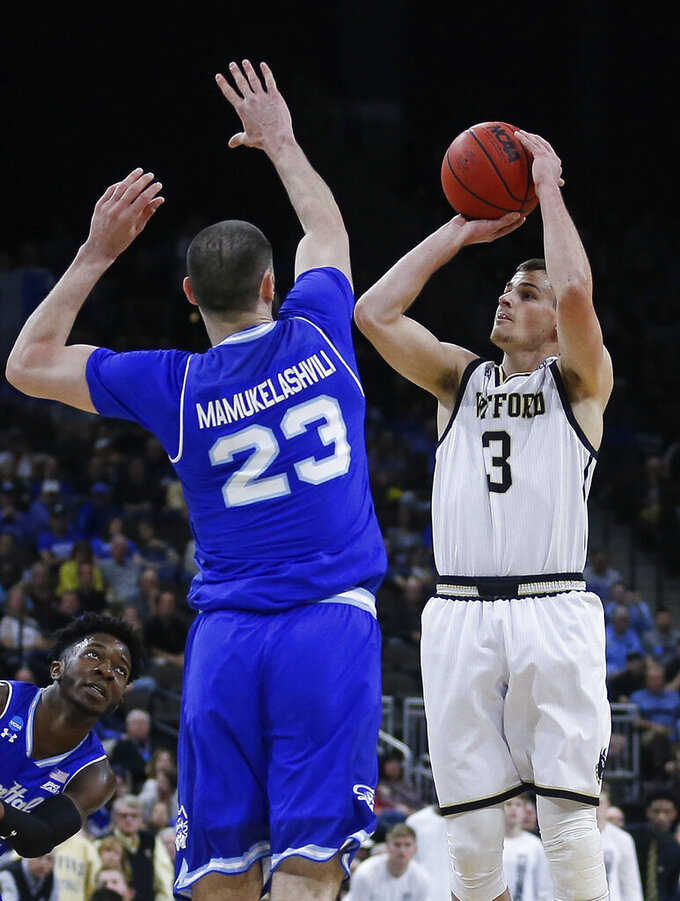 Wofford's Fletcher Magee (3) takes a 3-point shot over Seton Hall's Sandro Mamukelashvili (23) during the first half of a first-round game in the NCAA men's college basketball tournament in Jacksonville, Fla., Thursday, March 21, 2019. (AP Photo/Stephen B. Morton)