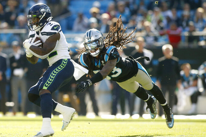 Carolina Panthers free safety Tre Boston, right, dives for Seattle Seahawks running back Chris Carson during the first half of and NFL football game in Charlotte, N.C., Sunday, Dec. 15, 2019. (AP Photo/Brian Blanco)