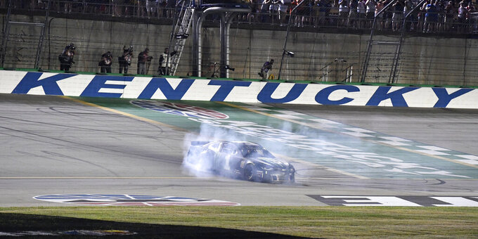 Kurt Busch does a burnout following his victory in the NASCAR Cup Series auto race at Kentucky Speedway in Sparta, Ky., Saturday, July 13, 2019. (AP Photo/Timothy D. Easley)