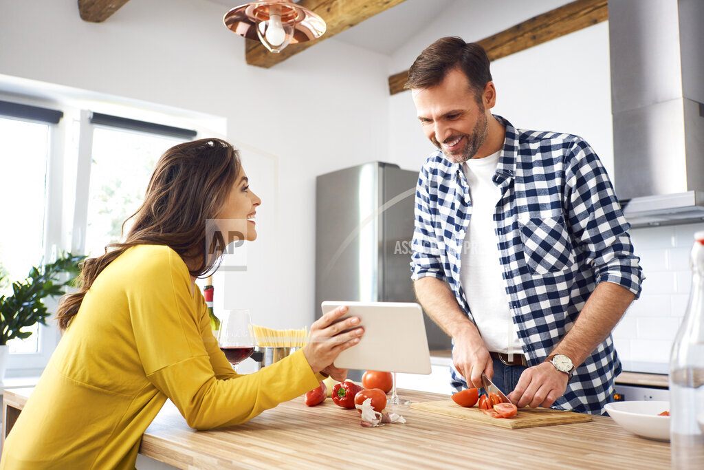 Affectionate couple in kitchen, preparing spaghetti toghether, using digital tablet