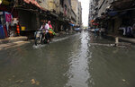 A motorcyclist drives through a street flooded by heavy rainfall in Karachi, Pakistan, Sunday, Aug. 9, 2020. Three days of heavy monsoon rains triggering flash floods killed at least dozens people in various parts of Pakistan, as troops with boats rushed to a flood-affected district in the country's southern Sindh province Sunday to evacuate people to safer places. (AP Photo/Fareed Khan)