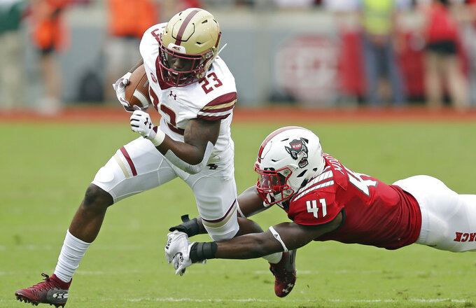 Boston College's Travis Levy (23) runs the ball while North Carolina State's Isaiah Moore (41) dives during the first half an NCAA college football game in Raleigh, N.C., Saturday, Oct. 6, 2018. (AP Photo/Gerry Broome)