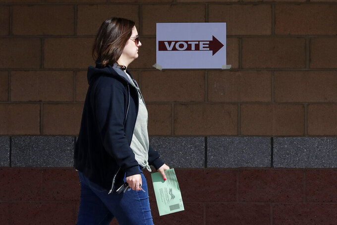 FILE - In this March 17, 2020, file photo, an Arizona voter delivers her mail-in ballot at a polling station for the Arizona presidential preference election in Phoenix. In addition to their nationwide efforts to restrict voting access, Republican lawmakers in some key states are seeking greater control over the local mechanics of elections, from voter registration to certifying results. (AP Photo/Matt York, File)