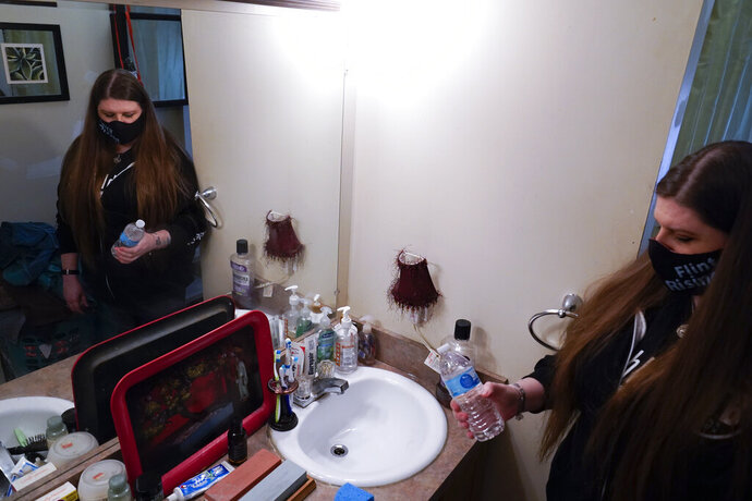 Melissa Mays grabs a bottle of water in the bathroom of her home in Flint, Mich., Wednesday, Jan. 13, 2021.  Some Flint residents impacted by months of lead-tainted water are looking past expected charges against former Gov. Rick Snyder and others in his administration to healing physical and emotional damages left by the crisis. (AP Photo/Paul Sancya)