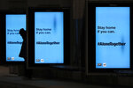 A pedestrian waits in silhouette for a Chicago Transit Authority bus as several COVID-19 public service messages are projected on screens at the bus stop Thursday, April 30, 2020, in Chicago.  (AP Photo/Charles Rex Arbogast)