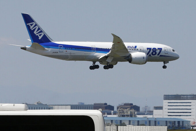 FILE - In this April 28, 2013, file photo, a Boeing 787 plane of the All Nippon Airways, ANA, prepares to land after a test flight at Haneda Airport in Tokyo. Domestic sponsors have already contributed a record of $3.3 billion to help pay for the Tokyo Olympics. That's at least twice as much as any previous Games. Now they're being asked to pay millions more to cover some of the soaring costs of the one-year postponement. Among the domestic sponsors is Japanese airline ANA, which posted losses of $1.8 billion through the first half of the fiscal year. (AP Photo/Shizuo Kambayashi, File)