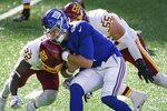 Washington Football Team's Deshazor Everett (22) and Cole Holcomb (55) tackle New York Giants quarterback Daniel Jones (8) during the second half of an NFL football game Sunday, Oct. 18, 2020, in East Rutherford, N.J. (AP Photo/John Minchillo)