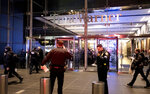 After it was determined the building was safe, New York City police officers stand by at the Time Warner Center as people reenter the lobby in New York Thursday, Dec. 6, 2018, after a bomb threat was called into the building and occupants were evacuated, including CNN employees. Police units swept the building with the NYPD bomb squad on standby. (AP Photo/Craig Ruttle)