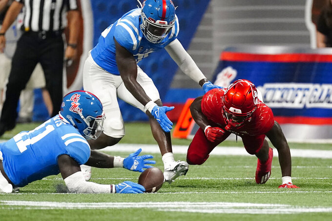Mississippi linebacker Austin Keys (11) recovers a fumble by Louisville running back Hassan Hall (19) right, as Ashanti Cistrunk (36) looks on during the first half of an NCAA college football game, Monday, Sept. 6, 2021, in Atlanta. (AP Photo/John Bazemore)