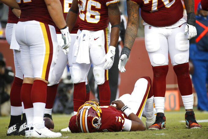Washington Redskins quarterback Dwayne Haskins, bottom, lies on the ground after being sacked by New York Giants linebacker Lorenzo Carter, not visible, during the second half of an NFL football game, Sunday, Dec. 22, 2019, in Landover, Md. Haskins walked to a cart and was taken off the field after the play. (AP Photo/Patrick Semansky)