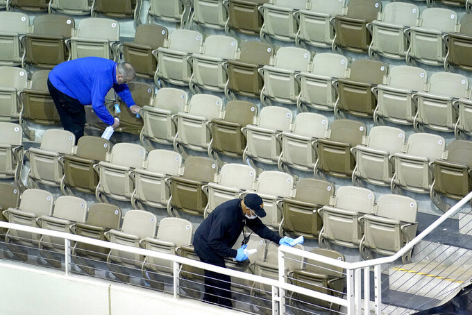 Workers at the Indiana Farmers Coliseum in Indianapolis, sanitize seats between first round NCAA college basketball tournament games Friday, March 19, 2021. (AP Photo/Charles Rex Arbogast)