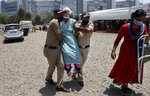 FILE- In this April 24, 2021, file photo, police personnel help an elderly woman outside a vaccination center in Mumbai, India. Misinformation about the coronavirus is surging in India as the death toll from COVID-19 rises. Fueled by anguish, distrust and political polarization, the claims are further compounding India's crisis. (AP Photo/Rajanish Kakade, File)