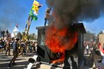 Protesters burn property in front of the U.S. embassy compound, in Baghdad, Iraq, Tuesday, Dec. 31, 2019. Dozens of angry Iraqi Shiite militia supporters broke into the U.S. Embassy compound in Baghdad on Tuesday after smashing a main door and setting fire to a reception area, prompting tear gas and sounds of gunfire. (AP Photo/Khalid Mohammed)
