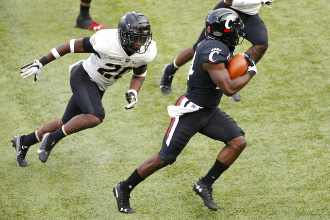 Cincinnati running back Jerome Ford, right, cuts up field past Army defender Marquel Broughton to score a touchdown during the second half of an NCAA college football game Saturday, Sept. 26, 2020, in Cincinnati, Ohio. Cincinnati beat Army 24-10. (AP Photo/Jay LaPrete)