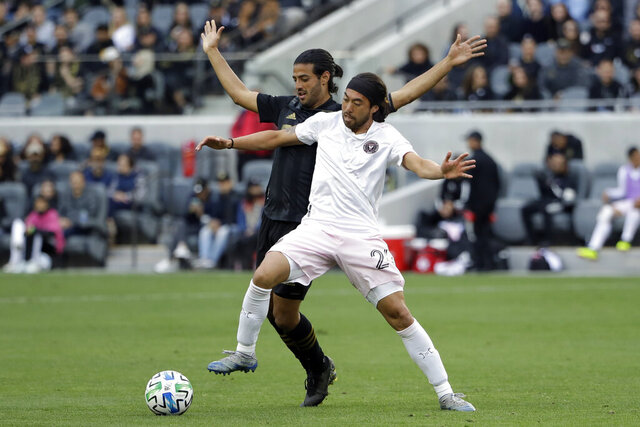 Los Angeles FC's Carlos Vela, left, defends on Inter Miami CF's Lee Nguyen during the second half of an MLS soccer match Sunday, March 1, 2020, in Los Angeles. (AP Photo/Marcio Jose Sanchez)