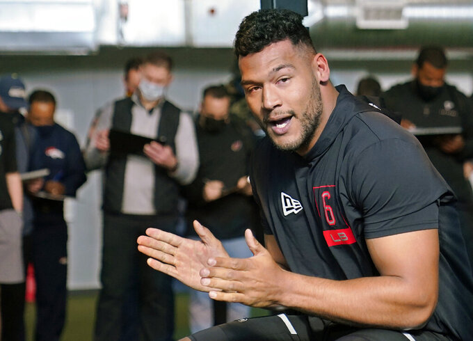 FILE - Tulsa linebacker Zaven Collins claps after completing the bench press during NFL football pro day in Tulsa, Okla., in this Friday, April 2, 2021, file photo. Collins is a possible first round pick in the NFL Draft, April 29-May 1, 2021, in Cleveland. (AP Photo/Sue Ogrocki, File)