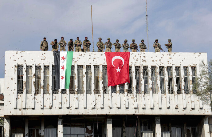 Turkish soldiers, right, and Turkey-backed opposition fighters stand atop a building next to their flags in Syrian town of Ras al Ayn, northeastern Syria, Wednesday, Oct. 23, 2019. Turkish media reports say Turkish troops and their allied Syrian opposition forces are securing a town in northeast Syria after Syrian Kurdish fighters pulled out of the area.(Ugur Can/DHA via AP)