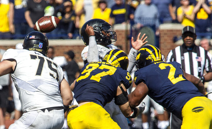 Army quarterback Kelvin Hopkins Jr., top, fumbles the ball, tackled by Michigan defensive linemen Aidan Hutchinson (97) and Carlo Kemp (2), in the second overtime period of an NCAA football game in Ann Arbor, Mich., Saturday, Sept. 7, 2019. Michigan won 24-21 in overtime. (AP Photo/Tony Ding)