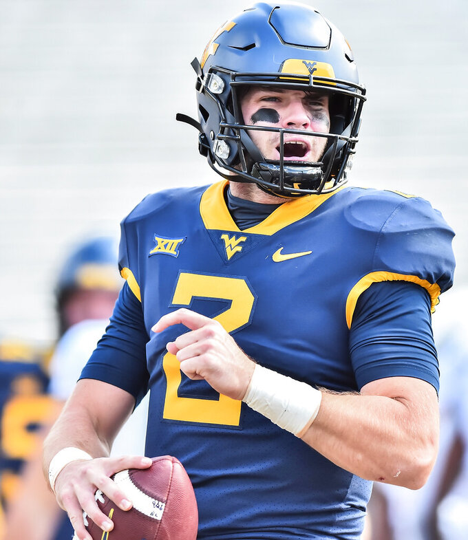 West Virginia quarterback Jarret Doege (2) reacts after scoring a touchdown against Baylor during an NCAA college football game, Saturday, Oct. 3, 2020, in Morgantown, W.Va. (William Wotring/The Dominion-Post via AP)